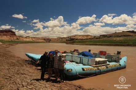 Group photo with river guides on Lake Powell after rafting Cataract Canyon with Western River Expeditions. Rafts on the Colorado River Colorado River in the background.