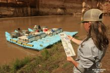 Photographer Claire Lessiau studying the rafting map of the Cataract Canyon on the bank of the Colorado River, with the rafts in the background, Western River Expeditions, USA.
