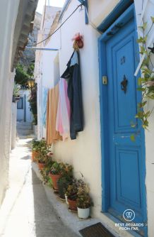 Blue door and laundry drying against a white wall in Anafiotika, Athens, Greece.