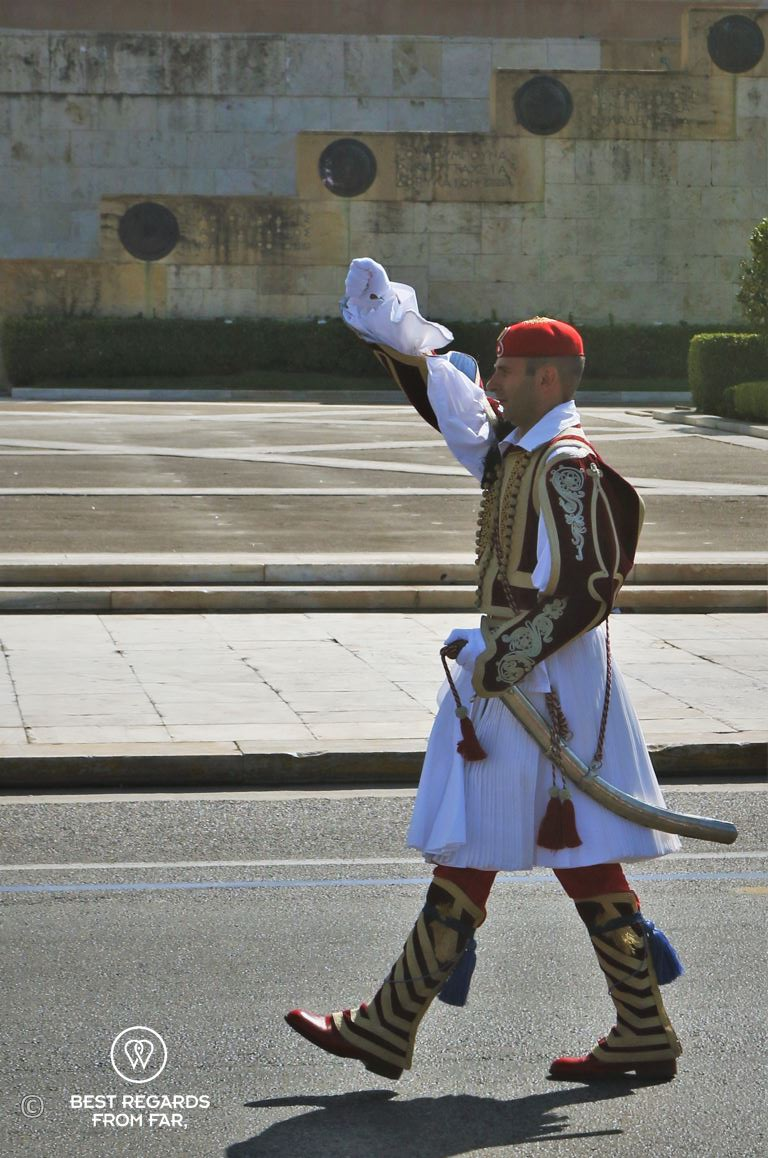 Man dressed in traditional clothes marching a square during the changing of the guards in Athens.
