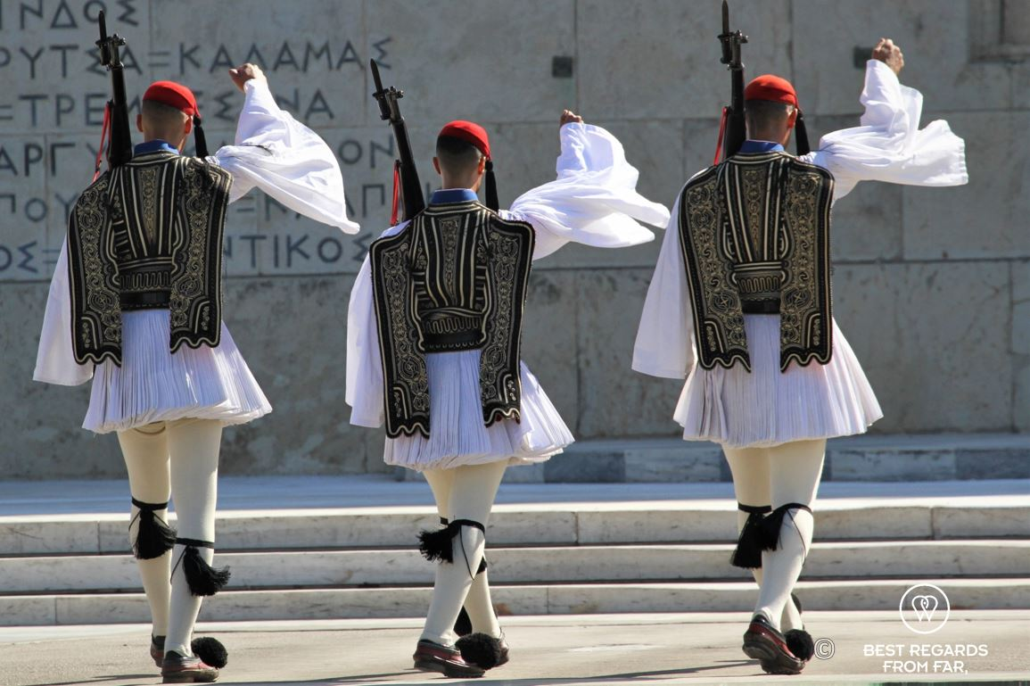Three man dressed in traditional clothes marching a square during the changing of the guards in Athens.