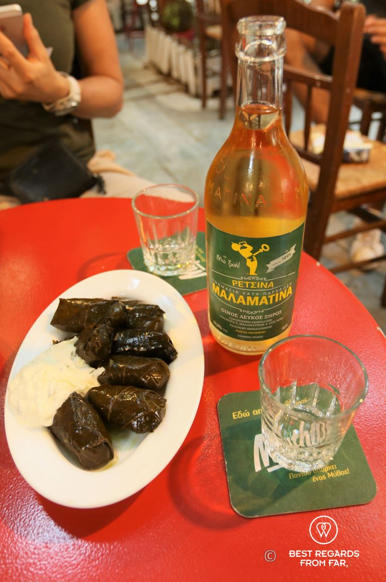 Red table with a bottle of Retsina, two glasses and a white plate of dolmades.