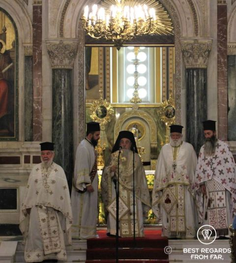Priests dressed in robes and black hats during mass in the Metropolitan Orthodox Cathedral, Athens, Greece