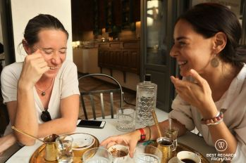 Two women laughing while reading coffee on a terrace in Greece.