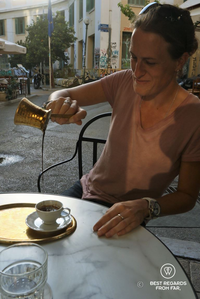 Woman pouring Greek coffee from high into a small cup on a terrace in Athens.