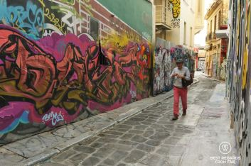 A man with red pants, grey jumber and green cap walking through a street covered in graffiti, Athens, Greece.