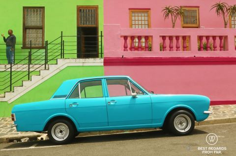 Oldtimer bright blue car parked in front of colourful houses of Bo Kaap with their typical architecture, Cape Town, South Africa.