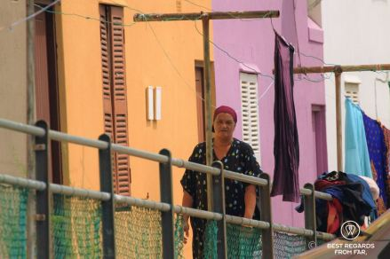 Woman with headscarf walking along drying laundry in front of a purple and orange house in Bo Kaap, Cape Town, South Africa.