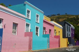 Row of colourful houses, pink, blue, yellow and purple, contrasting with Signal Hill and blue skies in Bo Kaap, Cape Town.