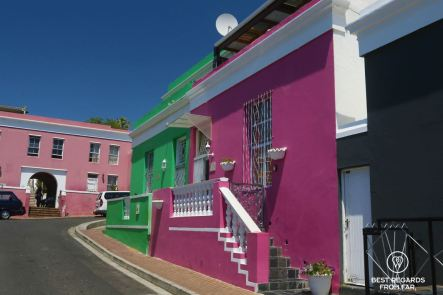 Bright purple and green house in Bo Kaap, Cape Town contrasting with a deep blue sky.