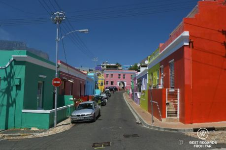 One-way street in Bo Kaap with colourful houses, blue skies and Table Mountain in Cape Town, South Africa.