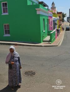 Muslim woman in dress and headscarf standin in the street among colourful houses with their Bo Kaap architecture, Cape Town, South Africa.