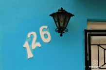 Number 126 written in white next to a black lamp contrasting on a bright blue wall of the typical architecture of Bo Kaap, Cape Town, South Africa.