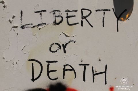 Black graffiti on a white wall reading Liberty or Death during the Hong Kong protests