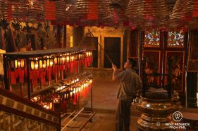 Monk hanging spiraled incense coils at the Man Mo Temple on Hong Kong Island. Red and gold tones dominate in a soft light.