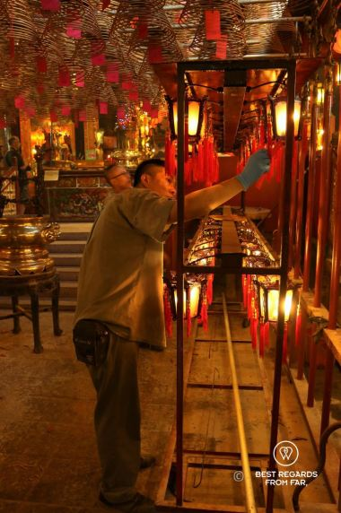 Monk arranging candles at the Man Mo Temple on Hong Kong Island. Red and gold tones dominate.