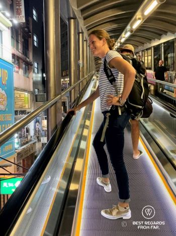Smiling tourists riding the mid-levels escalators to go up on Hong Kong Island