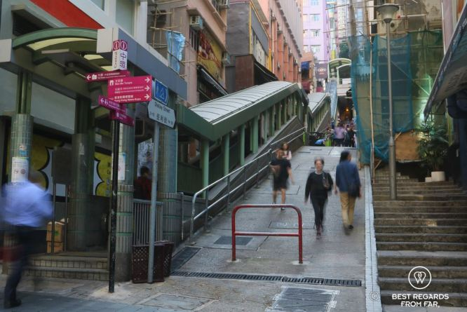 Hong Kongers walking fast by the mid-levels escalators on Hong Kong Island