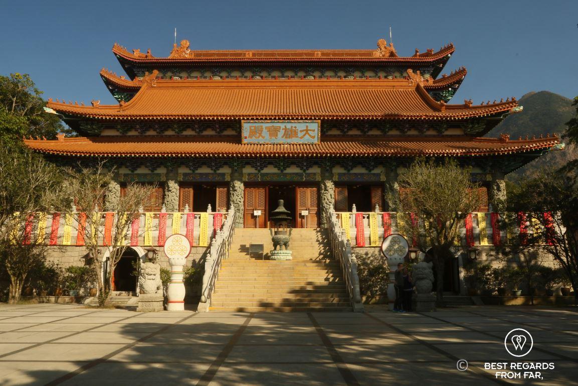 Po Lin monastery, orange roof in three layers, Chinese symbols above staircase, Lantau Island, Hong Kong.