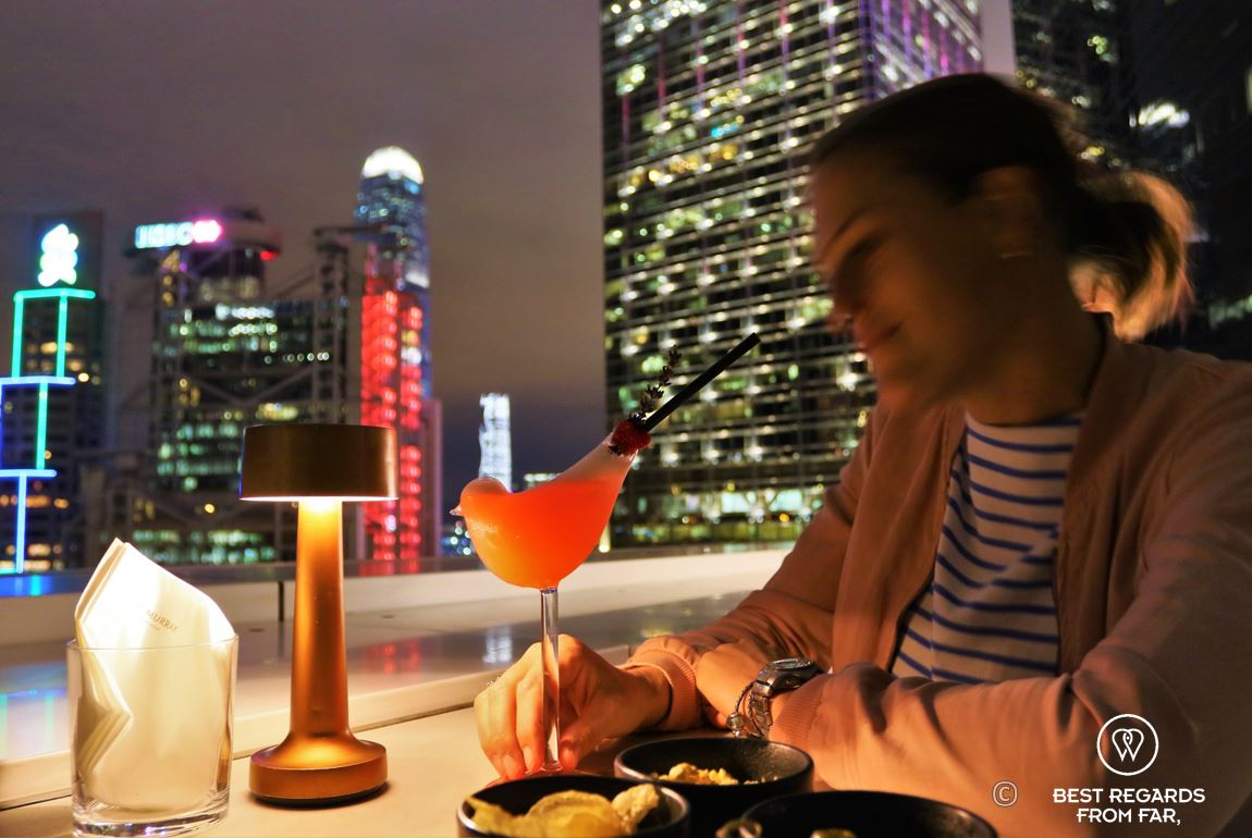 Female guest having a cocktail in a stylish bird glass at the Popinjays rooftop bar at night, the Murray Hotel, Hong Kong Island