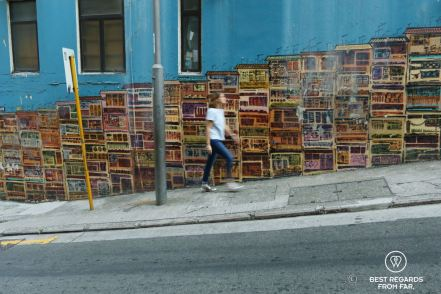 Fast-paced pedestrian walking in front of a mural street art showing buildings on Hong Kong Island