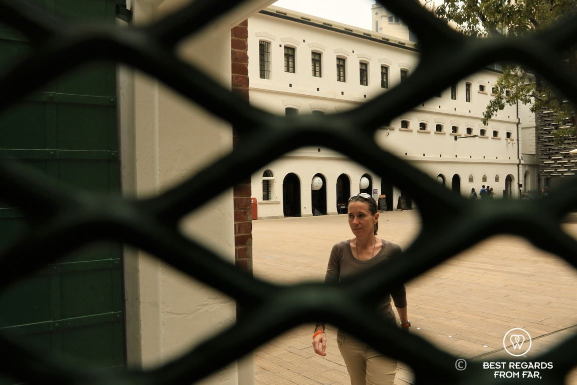 Visitor in the prison courtyard behind a fence at the former police quarters at Tai Kwun turned into a museum, Hong Kong