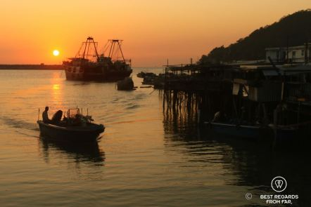 Sunset behind two boats, houses on stilts of the Tai O fishing village, Hong Kong.