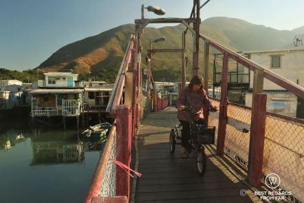 Local woman on a tricycle crossing a red bridge, Tai O fishing village, Lantau Island, Hong Kong