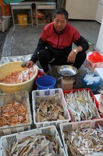 Local man selling dried fish in crates, Tai O fishing village, Lantau Island, Hong Kong