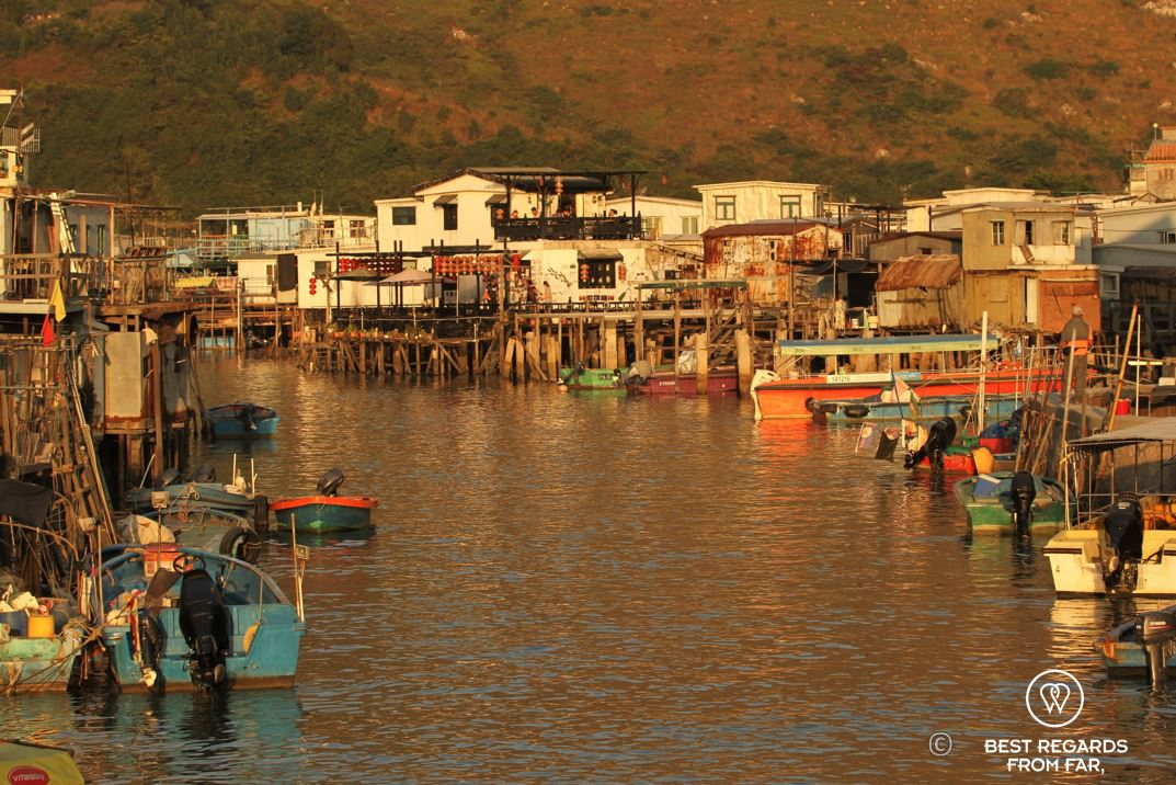 Water with colourful boats and on each side houses on stilts, Tai O fishing village, Lantau Island, Hong Kong.