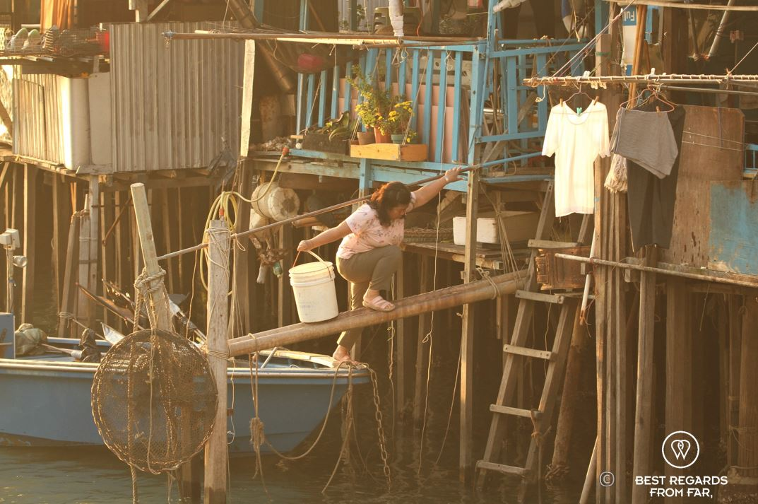 Woman with white bucket stepping of a blue boat in front of wooden houses on stilts, Tai O fishing village, Lantau Island, Hong Kong.