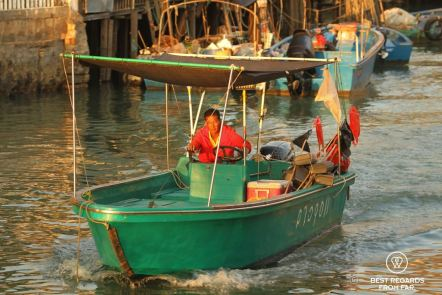 Man in red jacket steering a green boat at sunset, Tai O fishing village, Lantau Island, Hong Kong.