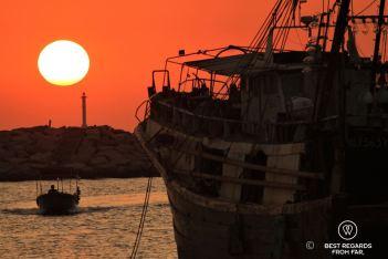 Sunset and orange sky behind a large fishing boat, a small boat and a lighthouse, Tai O fishing village, Lantau Island, Hong Kong.