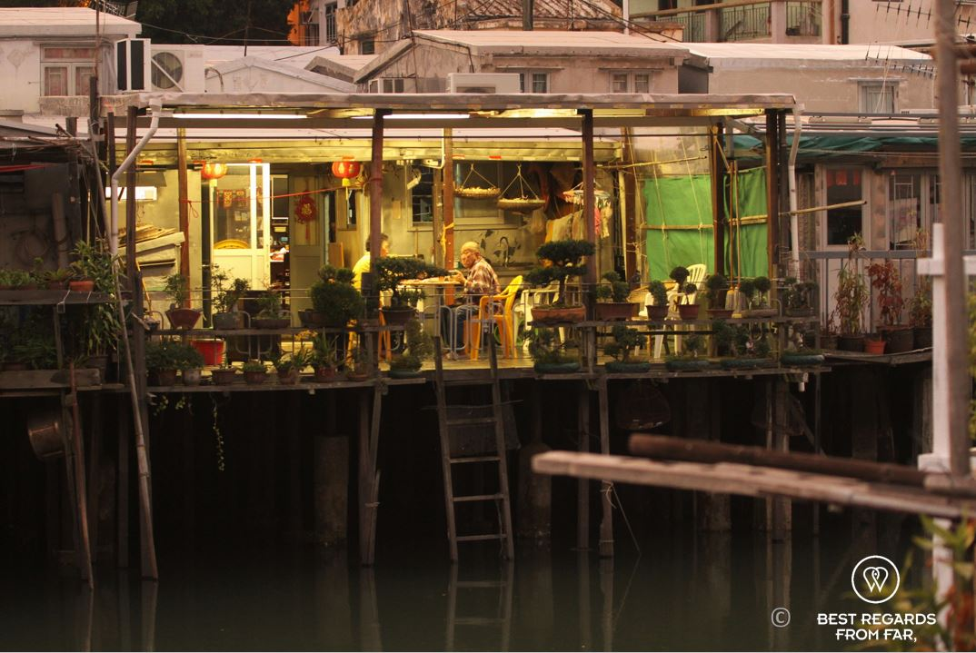 Man and woman having dinner outside on a wooden deck on stilts, Tai O fishing village, Lantau Island, Hong Kong