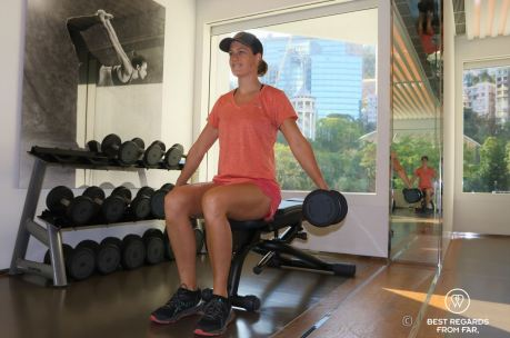 Guest working out with weights at the fitness center of the Murray Hotel overlooking the green Hong Kong park