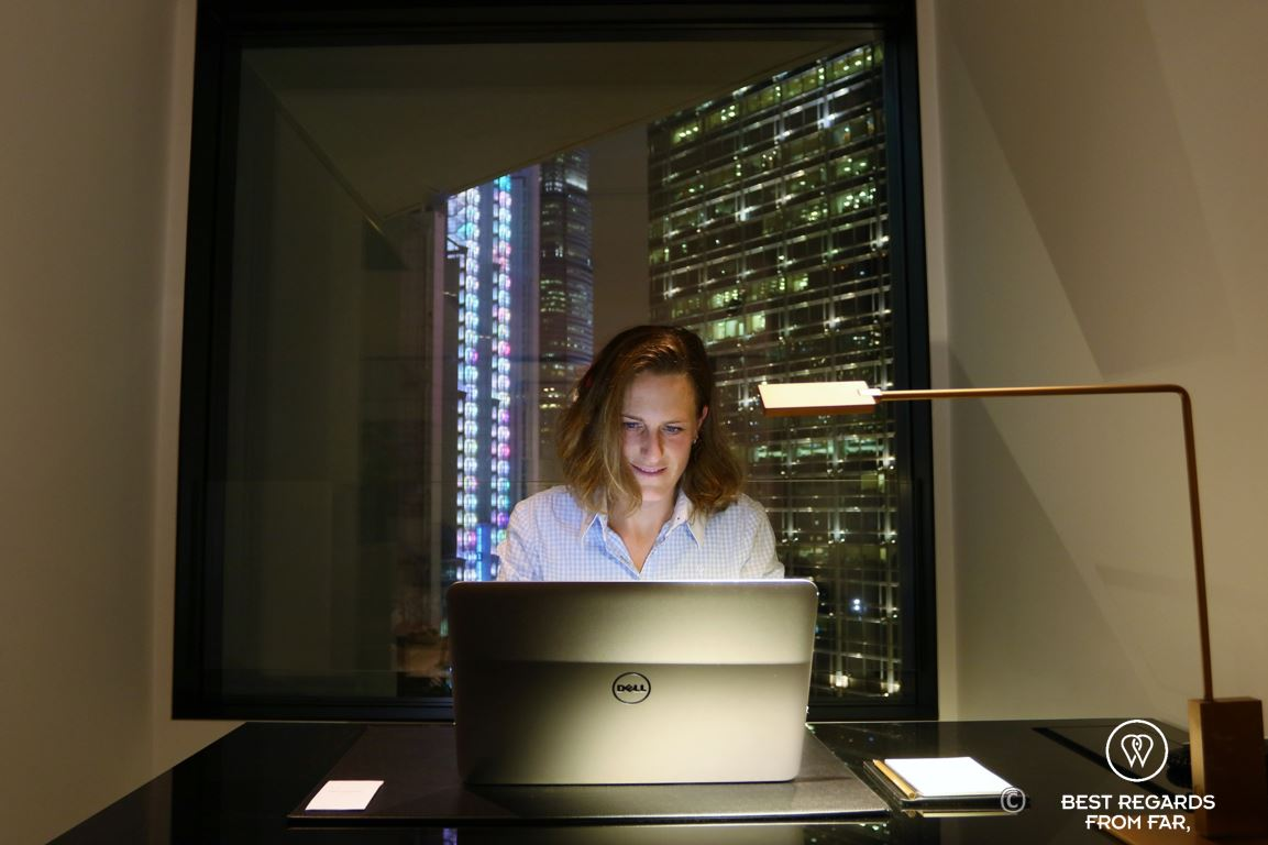 Guest at the desk in a hotel room of the luxurious Murray hotel on Hong Kong Island working on a laptop at night