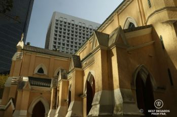The old architecture of Saint John's Cathedral in the foreground and The modern Murray Hotel in the background in Hong Kong