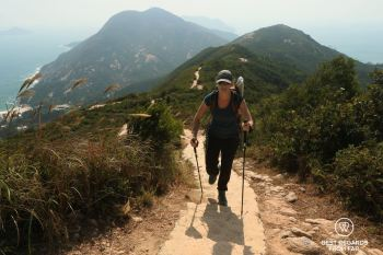Hiker walking the Dragon's Back trail in Hong Kong with hiking poles