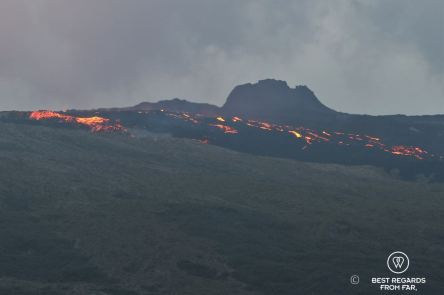 The Furnace Peak volcano in eruption in with the bright red lava in fusion flowing down the dark basalt slopes