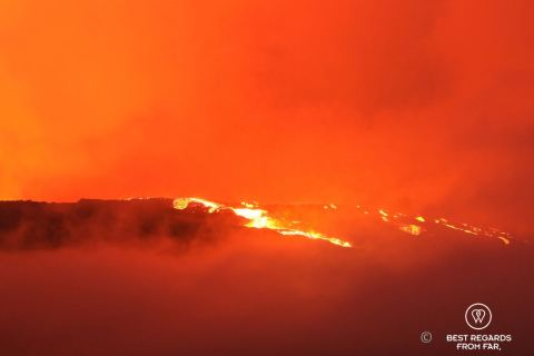 The Furnace Peak volcano in eruption in with the bright red lava in fusion and the red sky
