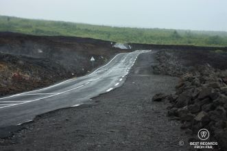The smoking hot road of lavas crosses black basalt rock by the ocean on the volcanic Reunion Island