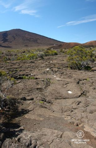The summit of Furnace Peak on Reunion Island with the hiking path leading to it and its white trail markers on dark basalt
