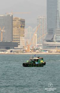 Working boat crossing the Hong Kong Bay with cranes in the background in Kowloon under construction