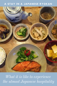 Food in small Japanese ceramics on a wooden table with a teapot.