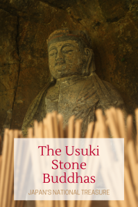 Buddha statue engraved in a rock with scent sticks in front of it and a red text on a white box saying: The Usuki Stone Buddhas, Japan's National Treasure