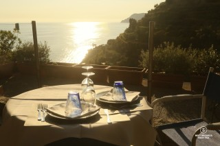 Dinner table set with a view at sunset in Italy