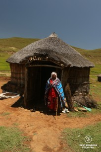 Traditional healer in front of her rondavel in Eastern Lesotho
