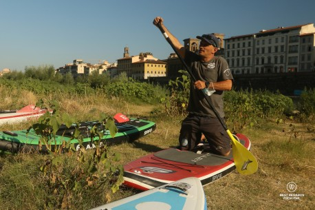 Tommaso Pucci at Toscana SUP explaining stand up paddling on the bank of the Arno River, Florence, Italy.