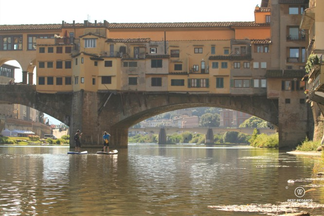 Stand up paddling the Arno River by the Ponte Vecchio in Florence, Italy.
