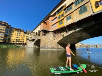 Writer Marcella van Alphen stand up paddling the Arno River by the Ponte Vecchio in Florence, Italy.